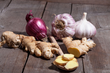 Giinger onions and garlic on wooden background