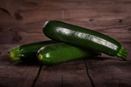 green Zuchinis on wooden table