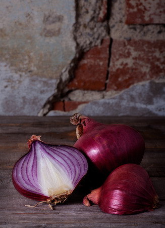 Onions on wooden table with stone wall as background