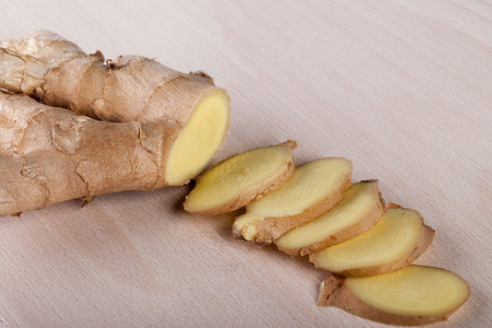 Ginger slices on wooden board Stock Photo