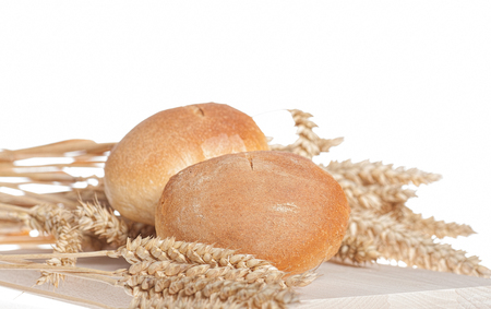 Buns and Wheat on wooden board over white background