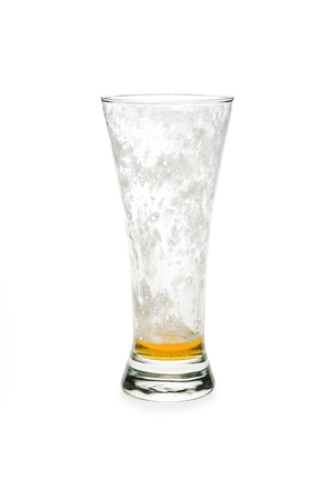 Almost empty beer glass isolated against white background. 免版税图像
