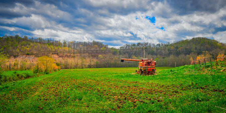 Old abandoned harvester in a field with trees in the background. Imagens