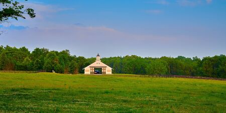 Kentucky horse barn with field in the foreground. Imagens
