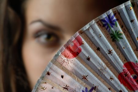 Fashion colored fan and out-of-focus face of the woman Stock Photo - 2679306