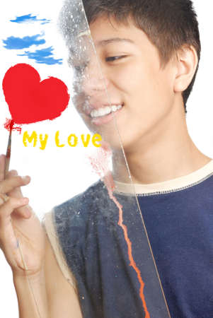Boy drawing the love symbols on the glass Stock Photo - 2699156