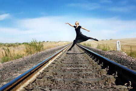 Ballet dancer jumping over the railway
