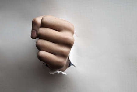 Paper broken by the fist as a symbol of the danger