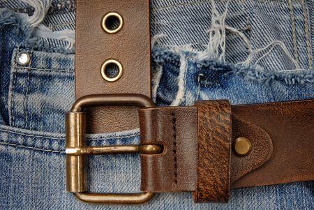 Close-up foto van de bruine band op oude blauwe jeans