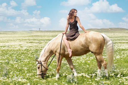Photo of the small woman on a big horse in summer field