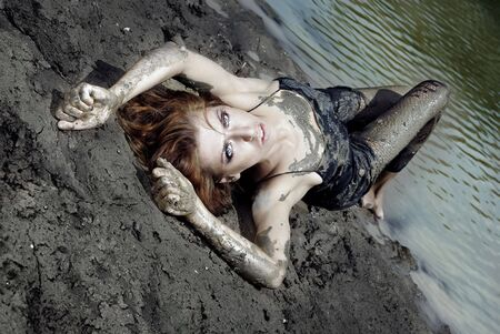 Dirty woman laying in the beach with passionate emotion