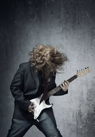 Electric guitar player on a trash background playing the rock music