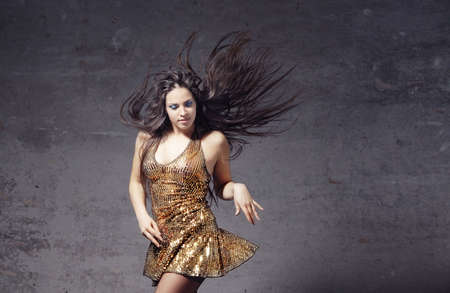 Active woman with long hair dancing on a trash background
