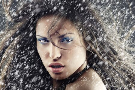 Sexy woman outdoors under the heavy snow in Christmas day