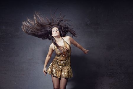 Woman dancing and moving her long hairs on a trashy background