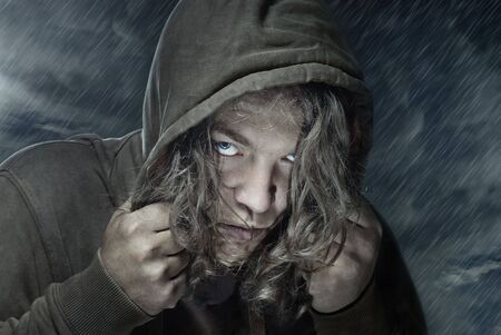 Portrait of the man under the rain. He could be assassin, thief, hitman, stranger, etc.