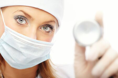 Doctor in protective mask and rubber gloves holding stethoscope