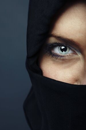 Woman with covered face looking to the camera