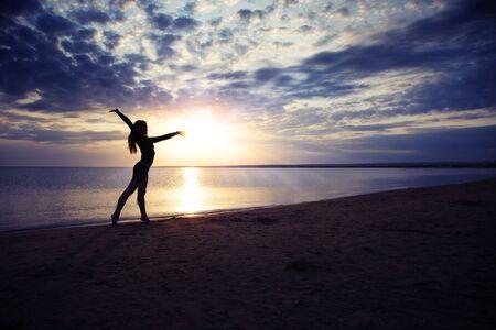 Nifty Dame macht Übung am Meer bei Sonnenuntergang Standard-Bild - 5429473