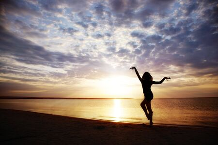 Woman doing healthy exercise during sunset
