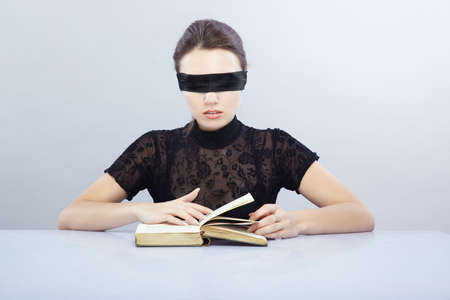 Woman with blindfold reading book indoors Standard-Bild
