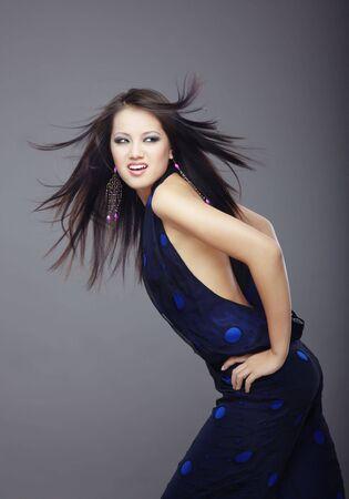 Elegante junge Dame mit geblasen Haare in der stilvollen Kleid auf einem dunklen Hintergrund  Standard-Bild - 6096384