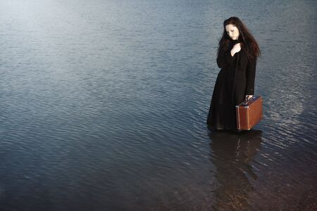 Solitude lady in the black coat holding travel bag and walking in the sea
