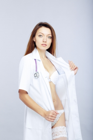 Sexy female doctor revealing medical uniform with stethoscope