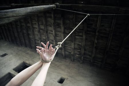 Woman hands hanged on the rope in ancient exterior photo