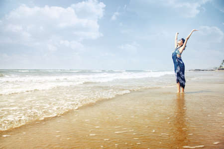 Happy lady standing in the water with hands up. Summer beach in Goa, India. Horizontal photo with vibrant colors Standard-Bild