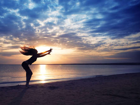 Dancing dynamic woman at the beach during sunset photo