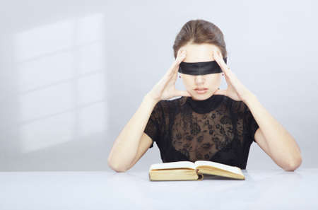 unclear: Woman with blindfold trying to read and understand foreign book.