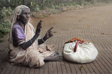 social outcast: Horizontal photo of the poor old woman sitting outdoors near her things