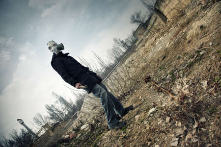 fallout: Human in the gas mask in postapoplectic landscape with toxic air. Vibrant color and moody darkness added
