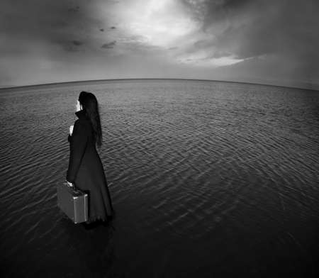 Sad woman with bag going into the sea. Black and white photo. Grain and distortion added for concept photo