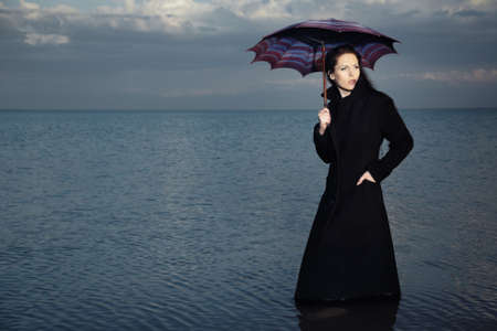 Single woman in the black coat standing in the water and holding umbrella. Creative symbol of the bad weather