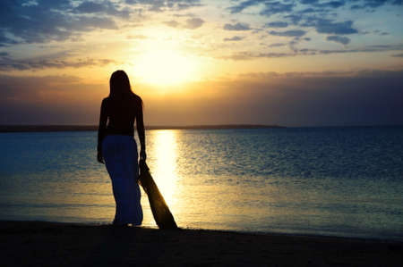 Silhouette of the single lady contemplating sunset at the beach. Vibrant color and twilight darkness  photo