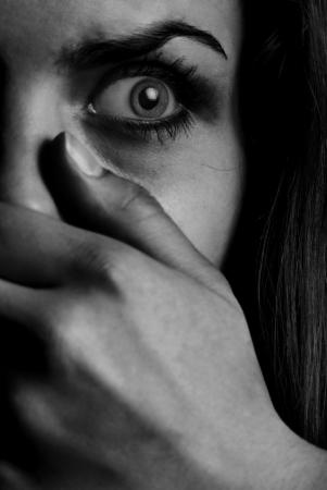 Horror zwart-wit foto van de bang vrouw met mond bedekt met de hand