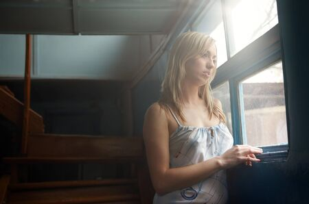 Alone lady standing at the window in the dark house. Daylight from the window photo