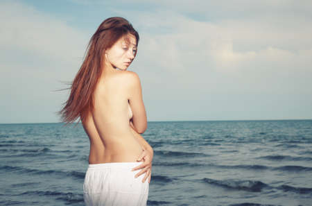 Topless lady in white shirt standing at the summer sea photo