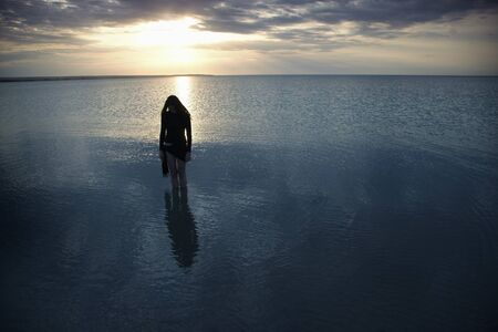 Silhouette of the single sad woman standing in the sea during sunset. Artistic colors and darkness added Standard-Bild