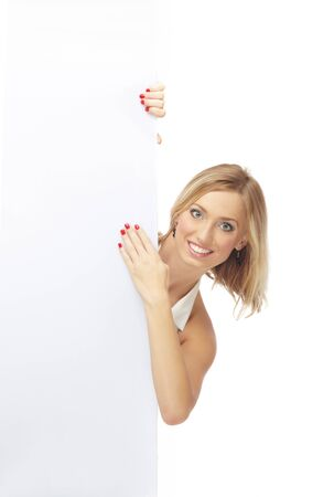 Smiling lady on a white background hiding behind white billboard photo