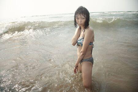 Wet brunette lady in bikini standing in the water photo