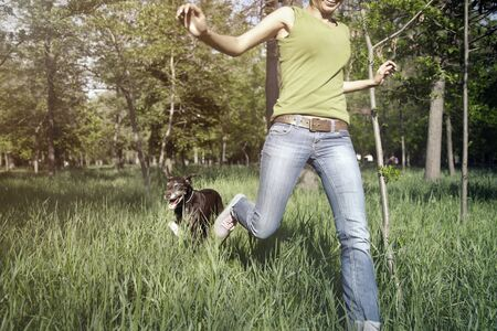 Happy girl outdoors running with her dog. Horizontal photo with daylight and natural colors Standard-Bild