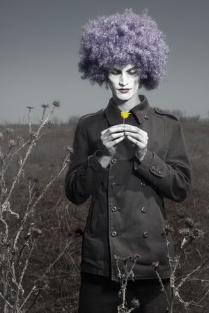Romantic photo of the clown outdoors holding yellow flower Standard-Bild
