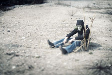 Single human in gas mask sitting in the desert near the dead plant. Concept of the futuristic environmental disaster. Special color added and shallow depth of field due to the tilt/shift lens for movie effect Stock Photo - 7428592