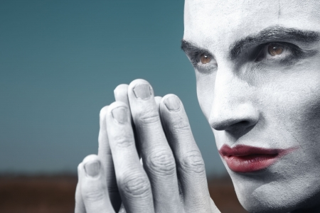 Angry vampire praying outdoors. Horizontal photo, special colors and darkness added