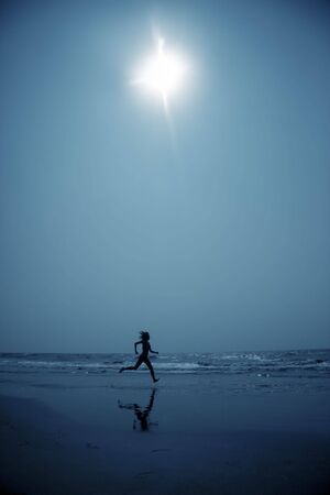 Woman at the beach running to the water in the deep dark night. Blue color toning added for coolness of the night Standard-Bild