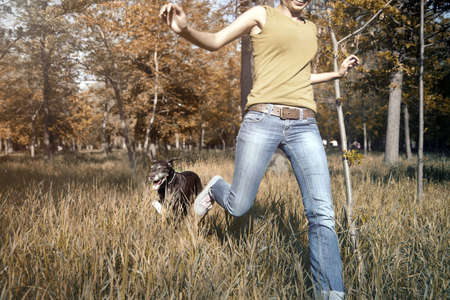 Happy young girl outdoors running with dog in the autumn forest Standard-Bild