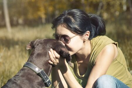 Happy lady outdoors kissing and pampering her dog. Spring sunlight used and cross-processed colors added